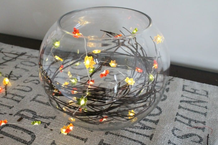 A clear glass globe with pretty miniature lights in fall colours.  DIY fall themed centerpiece, fall themed centerpieces, fall centerpieces diy,autumn decorating ideas, fall themed centerpieces, fall floral arrangements