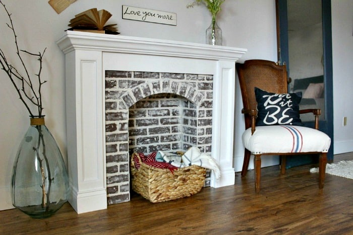 DIY faux fireplace made with faux brick and white moudling. Perfect for Christmas or fall decor.