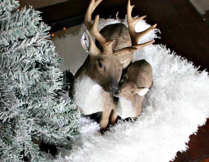 Easy DIY Christmas Centerpieces, this simple centerpiece has a rustic Christmas feel, made with faux snow, reindeer and small tree.
