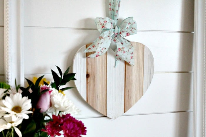 White and natural wood valentine hung from a frame for Valentine's day decor.