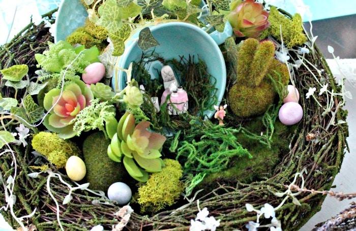Closeup of a teacup fairy garden, with a tiny table set.