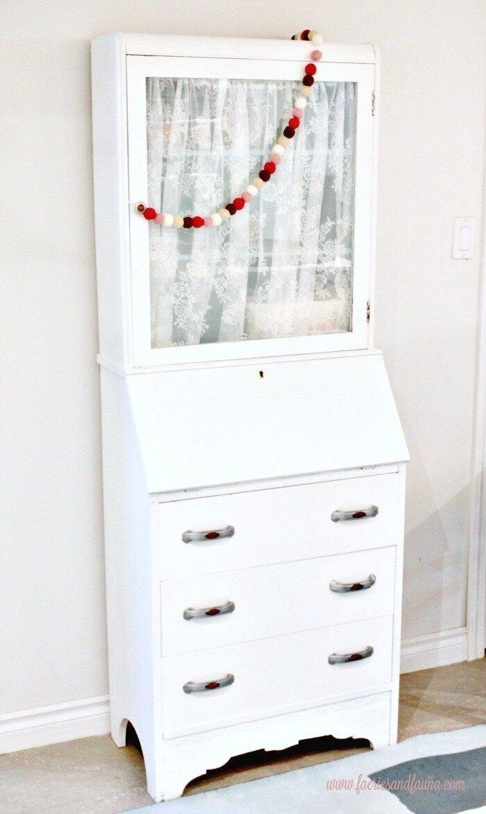 A art deco painted secretary receiving a furniture refinishing.