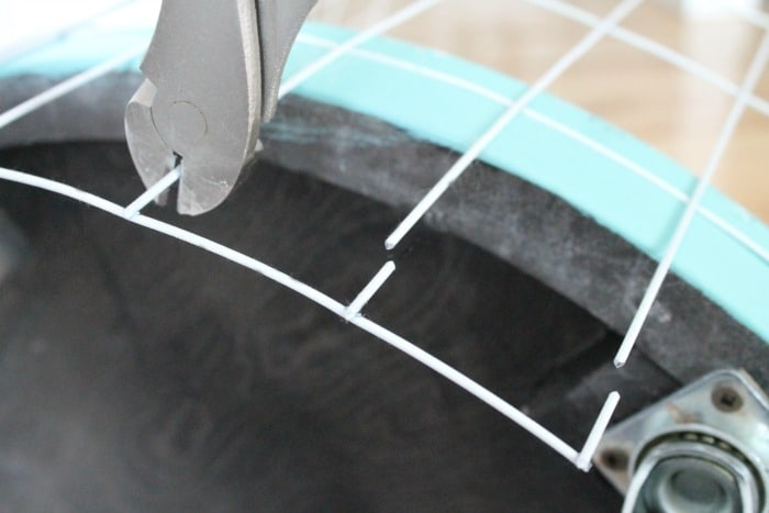Cutting and fitting wire on a DIY wire hamper with wheels.