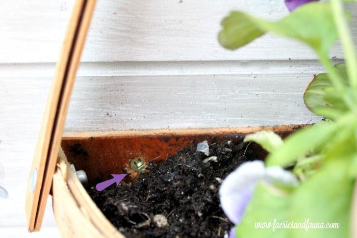 A hanging basket being mounted to the backdrop of a DIY planter