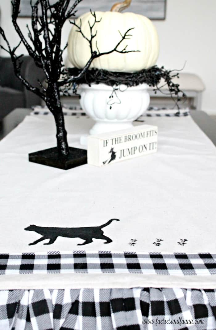 Handmade Halloween decoration idea. A homemade table runner with pretty buffalo print fabric and a painted black cat.