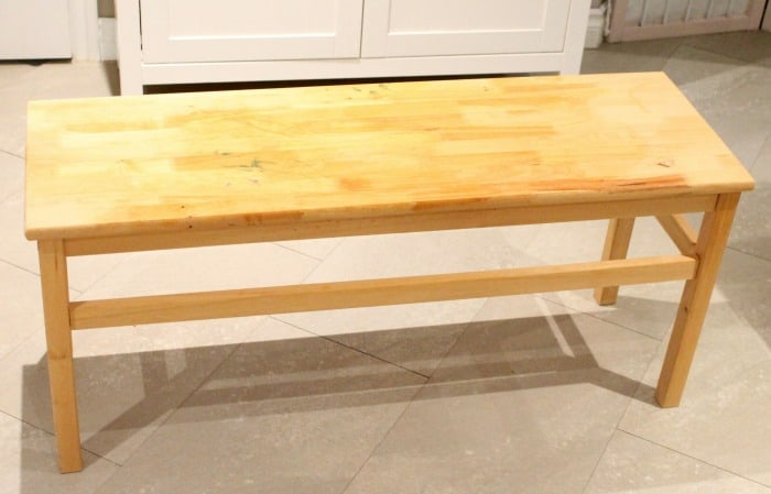 Wood bench before receiving a farmhouse bench update using paint and dropcloth
