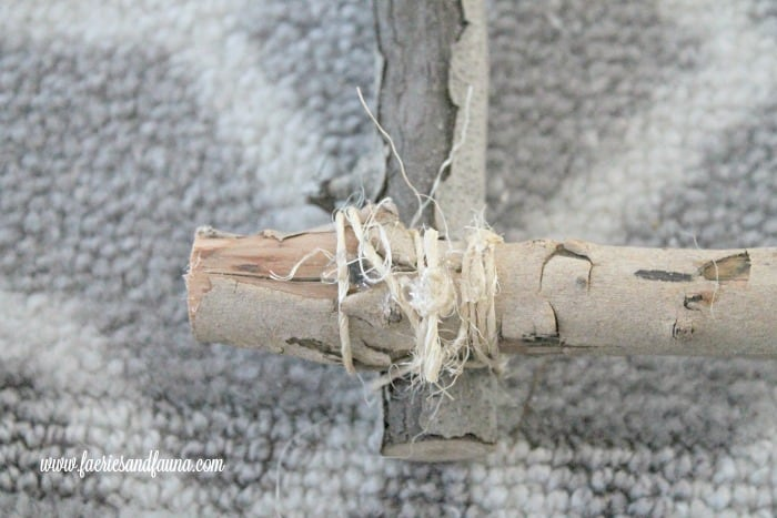 Binding the corners of a white birch DIY twig wreath for Christmas
