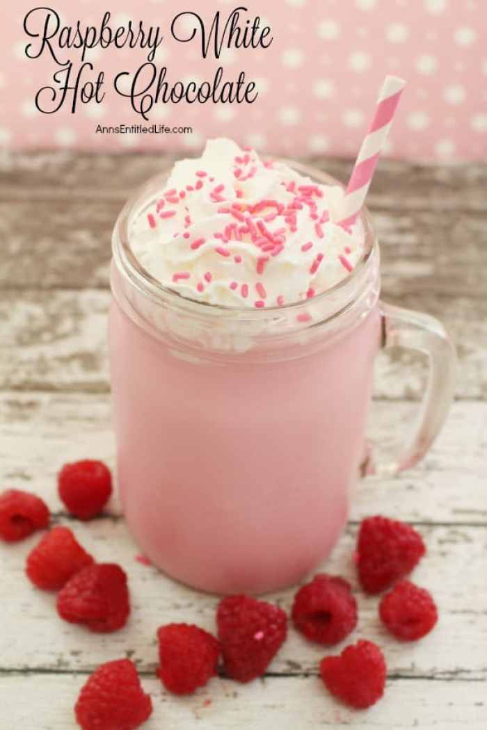 A pretty glass of Raspberry hot chocolate with whipped cream a sprinkles.