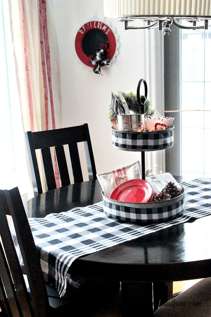 A Kitchen table decorated for Christmas with a DIY tiered tray centerpiece.