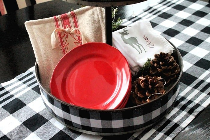 Christmas heating pad, red plates, Christmas napkins with reindeer and pine cones in a DIY Christmas Centerpiece for the Kitchen Table.