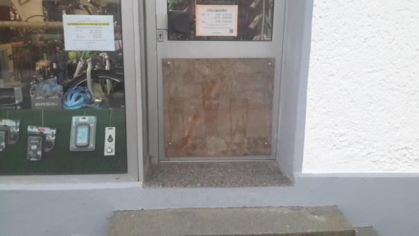 Zerstörte Scheibe in der Tür mit Platte verschlossen