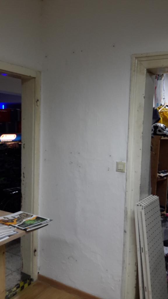 Dübel mit frischer Spachtelmasse in Löchern in der Wand fixiert