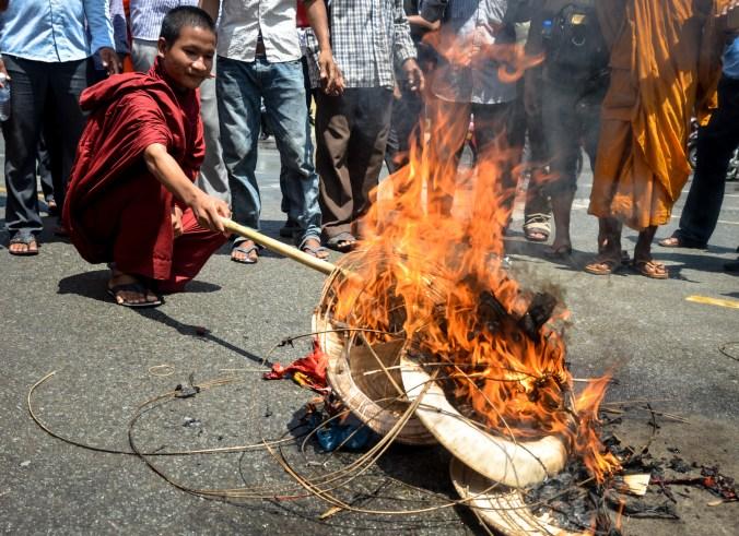 Monk tending a conical hat bonfire.