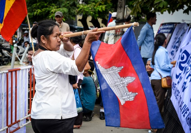 Woman pretends a Cambodian flag is a gun at the Vietnamese Embassy.