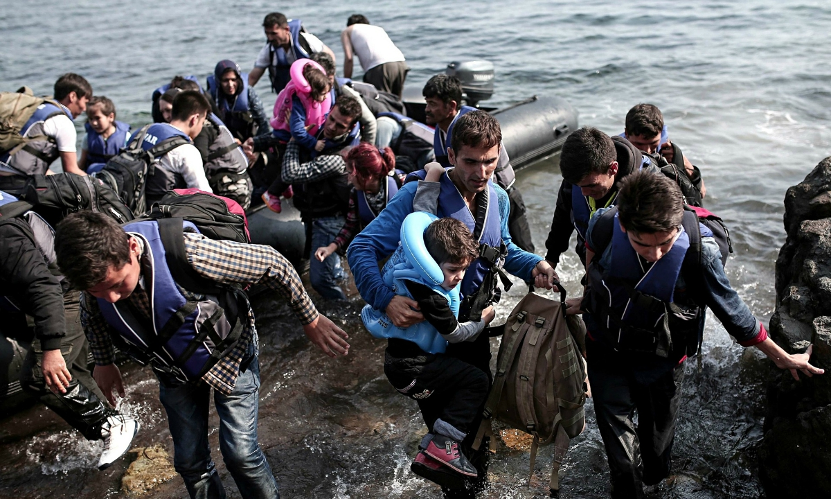 Syrian refugees coming ashore in Greece (photo: Angelos Tzortzinis/Getty)