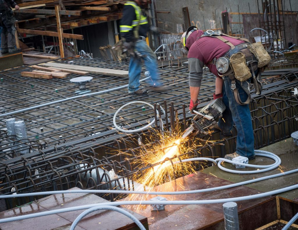 Construction worker cutting rebar