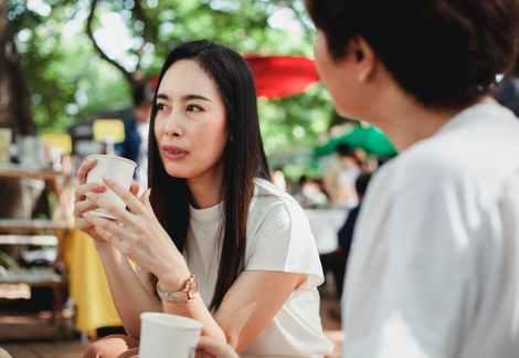positive asian women having coffee break in sunny street market