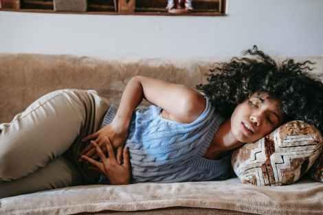 ethnic woman having stomach ache