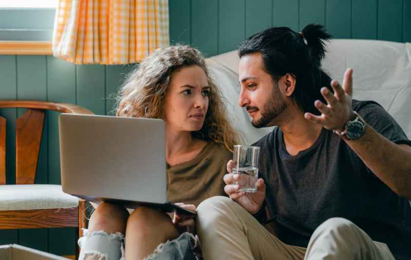 pensive couple with laptop sitting on floor