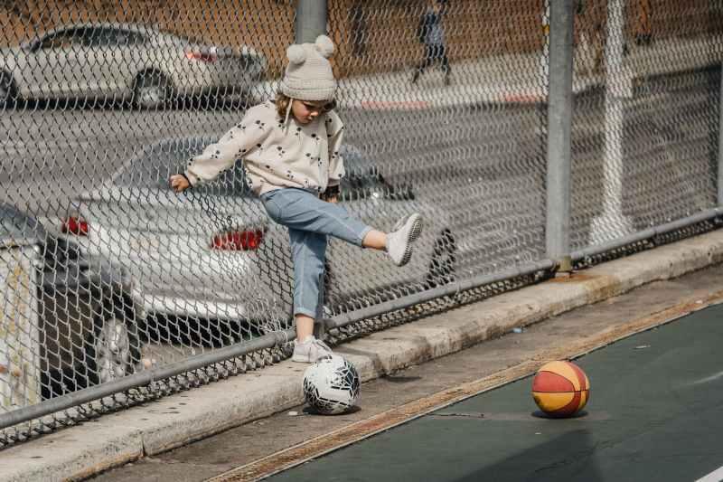 playful girl on playground with balls