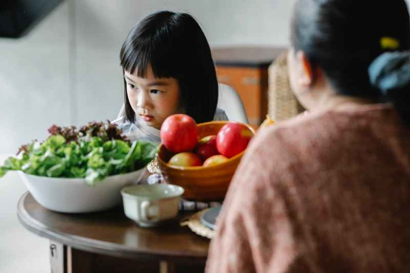 serious little ethnic girl sitting at table with mother during lunch and looking away