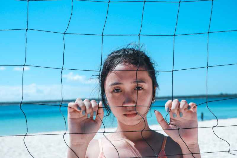 woman holding volleyball net