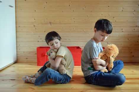 sad little siblings hugging toys on floor