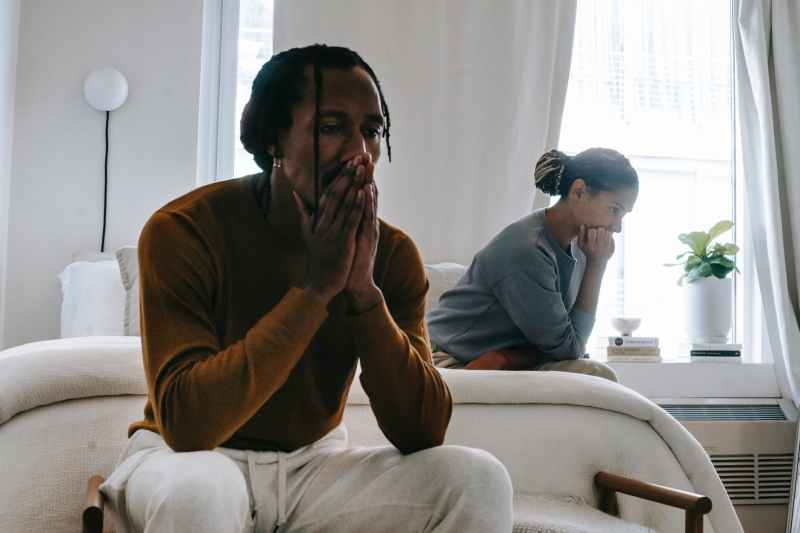 unhappy black couple sitting on bed after having argument