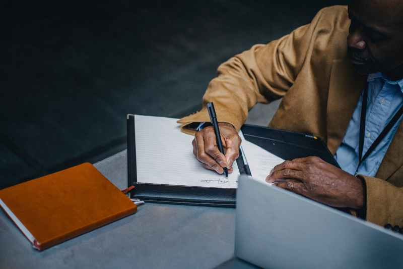 crop ethnic businessman taking note on paper sheet at table