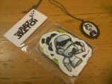 Bag of stickers with unusual graphic designs and a necklace. Same booth.
