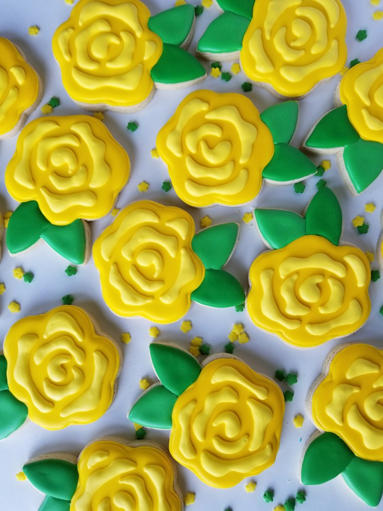 Yellow floral decorated sugar cookies with green leaves