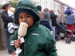 A kid enjoying elote or corn on the cob at a Christmas fiesta in Miguel Aleman