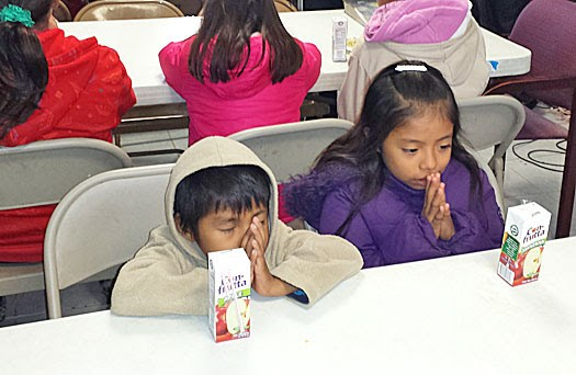 Kids praying before a meal at the Christmas fiestas in Mexico