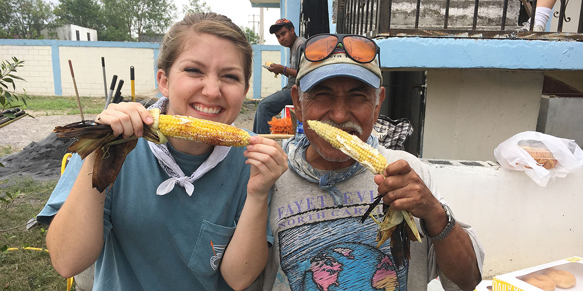 Friends enjoying a delicious corn on the cob or elote in Naranjito