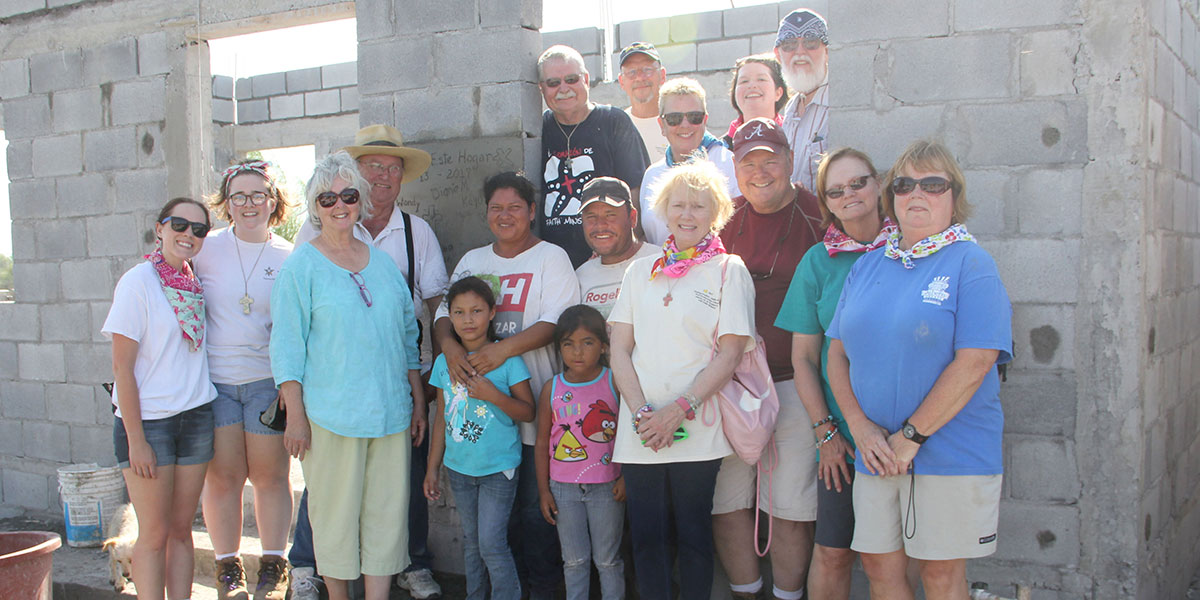 A team and a family in front of a completed house in Reynosa