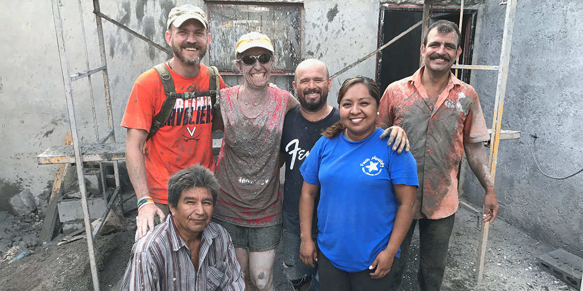 A team and a family after pouring a new roof on their house