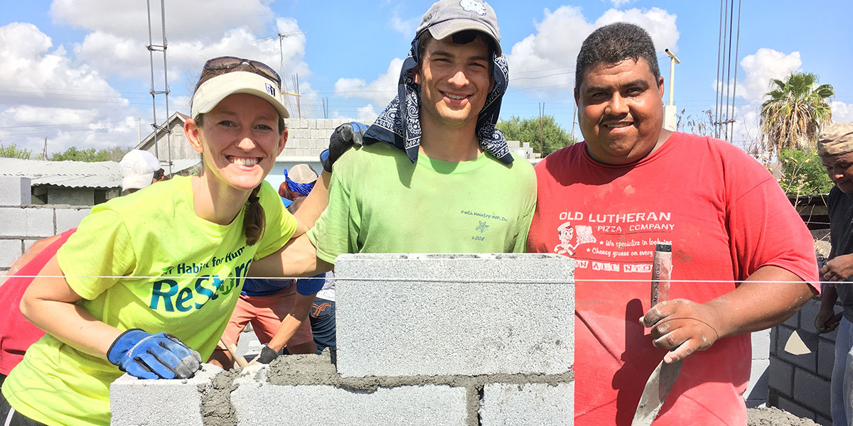 Friends working together to lay blocks to build a house in Reynosa