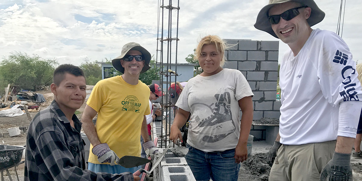 Friends laying block together to build a house in Reynosa
