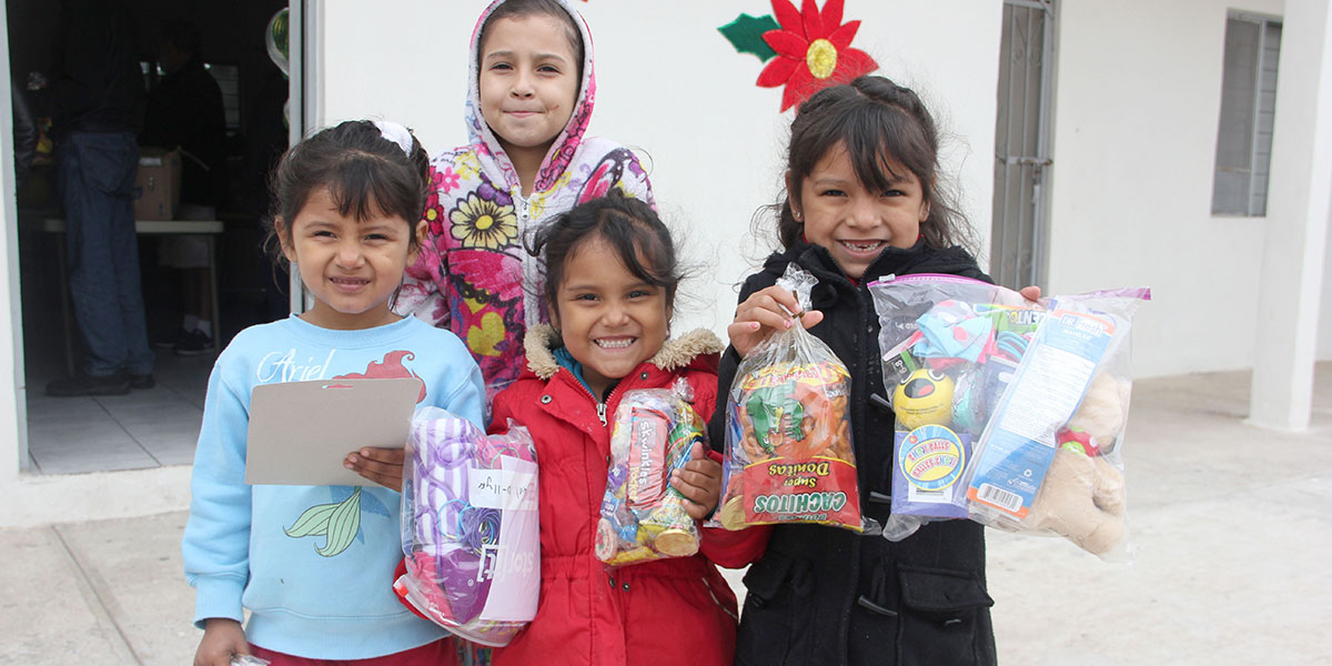 Girls with their candy and presents at the Christmas fiesta in Miguel Aleman