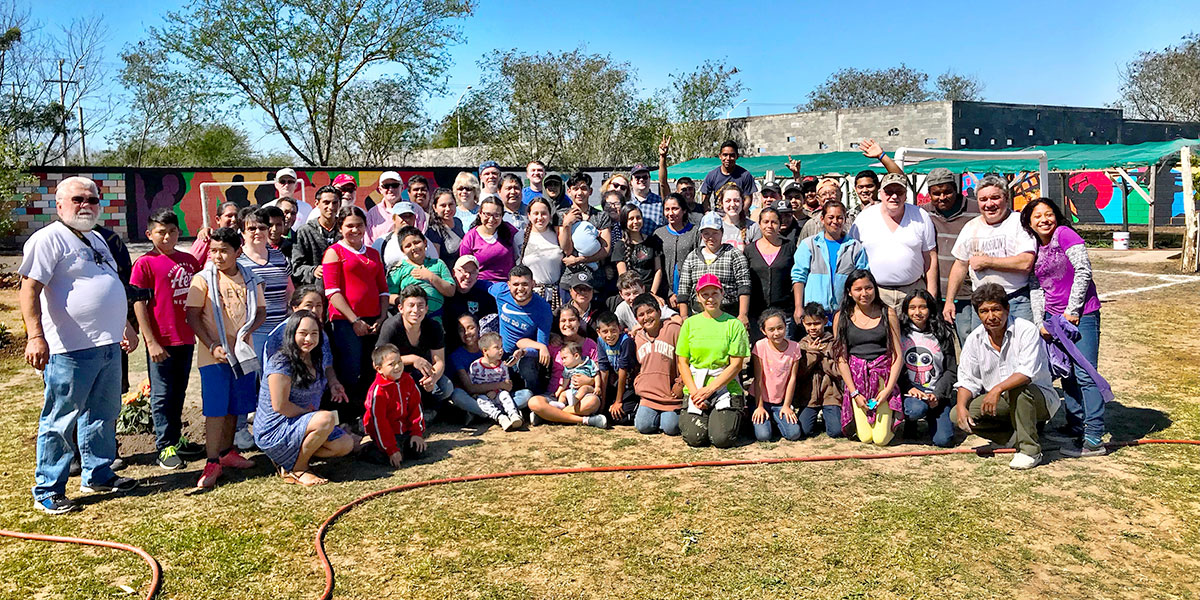 A team and the kids and adults of the church in Naranjito on a beautiful day