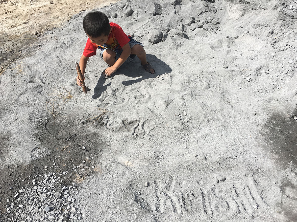 A little boy plays in the sand on the jobsite in Reynosa