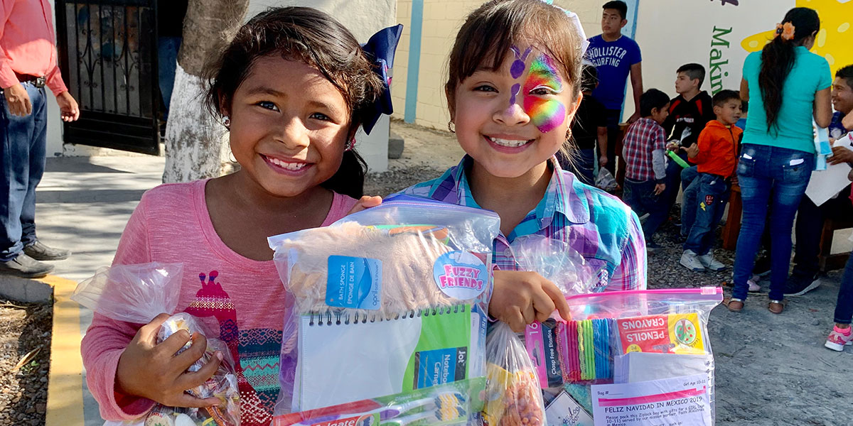 Girls with their Christmas gifts at the fiesta in Naranjito