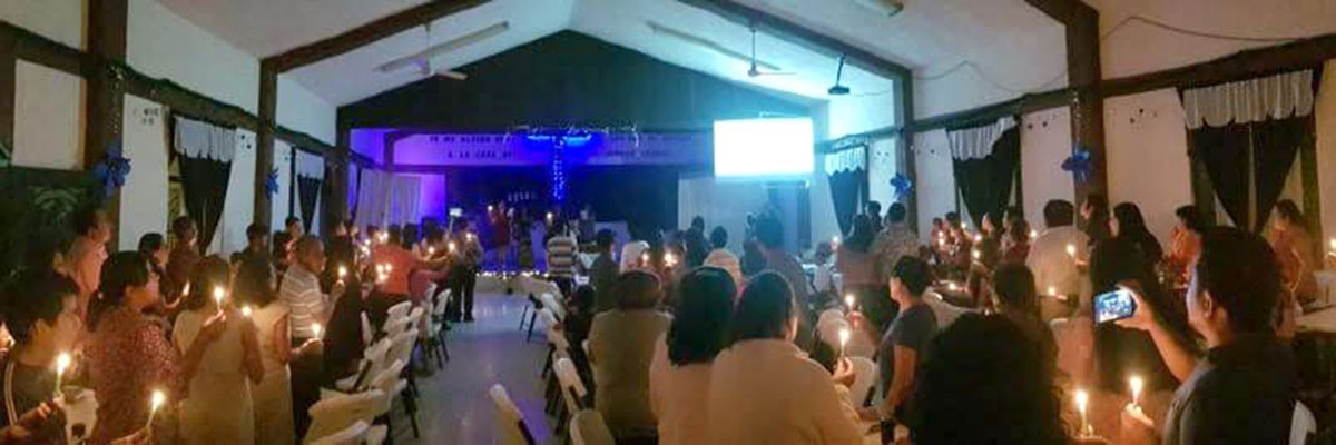 Singing Silent Night by candlelight at the church Christmas fiesta in Reynosa