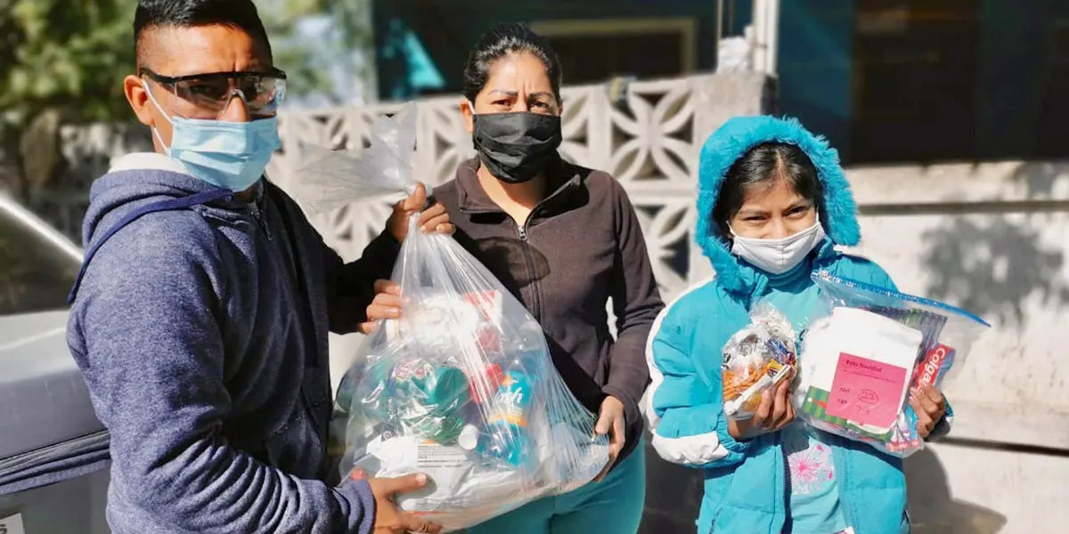 A family receiving a grocery package and gift bag for Christmas in Reynosa Mexico