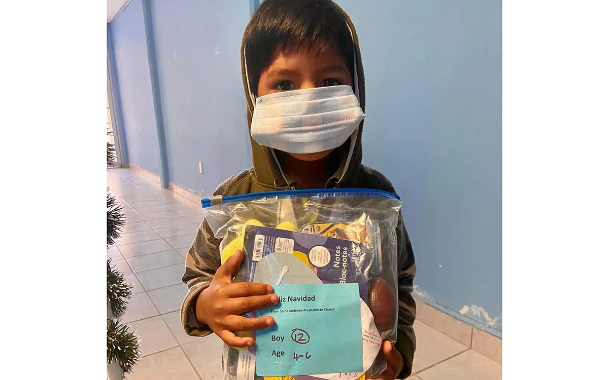A kid receiving a gift bag for Christmas in Reynosa Mexico