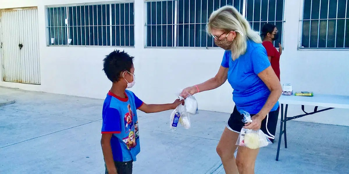 Our friend Amy helping to distribute meals to the kids at our nutrition program in Reynosa Mexico