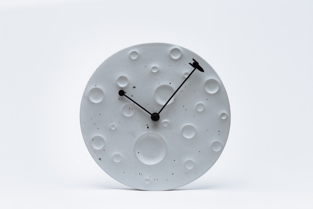 Wall clock made of concrete in the form of the moon ?Around the Moon in 60 Minutes? Active