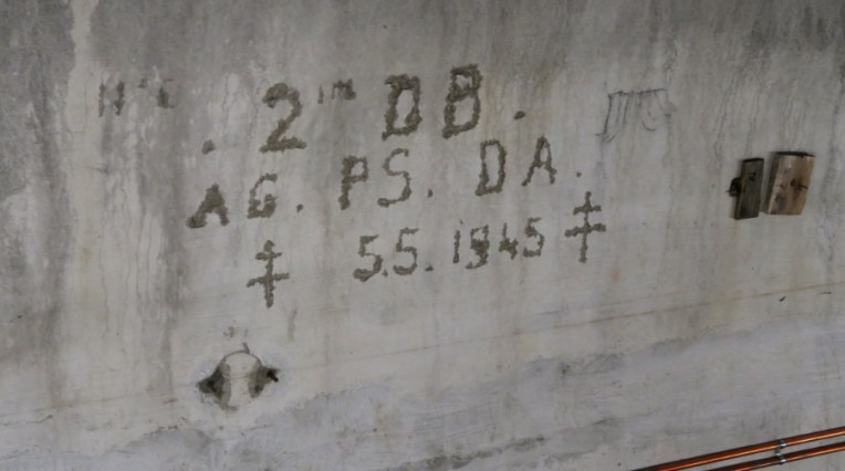 This is French graffiti. Notice the date: May 5, 1945, and the cross. It's the French Cross of Lorraine, which symbolized the French government in exile..