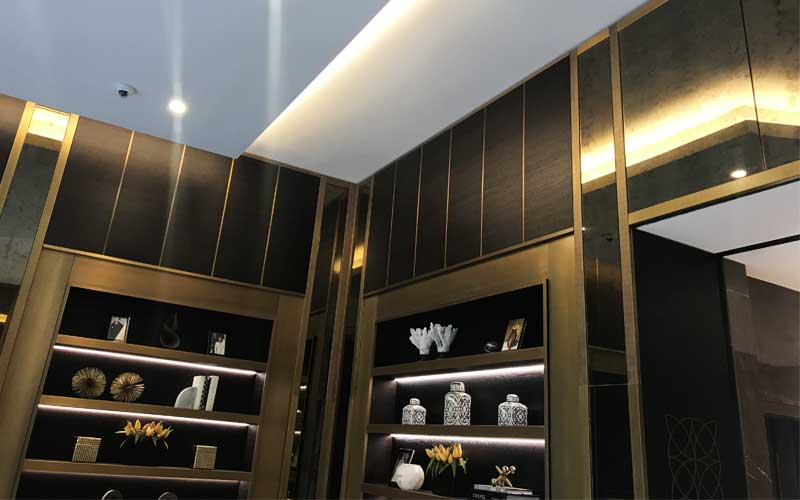 Dark wood joinery paneling with gold trim