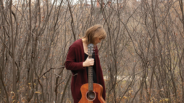 Jessica Heine holds her guitar with a backdrop of trees